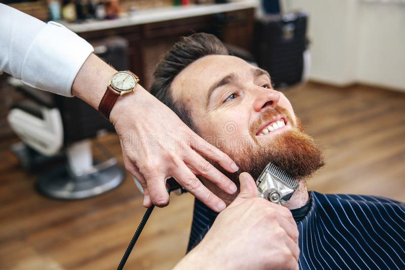 Un coiffeur rase la barbe de son client de la mani?re traditionnelle photos libres de droits