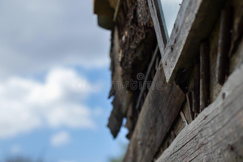 Un coin de la fenêtre de la vieille grange sur le fond du ciel nuageux photo stock