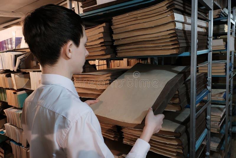 Un ?colier dans une chemise blanche retire un vieux livre d'une ?tag?re Un étudiant dans la bibliothèque ou dans la salle d'archi photos stock