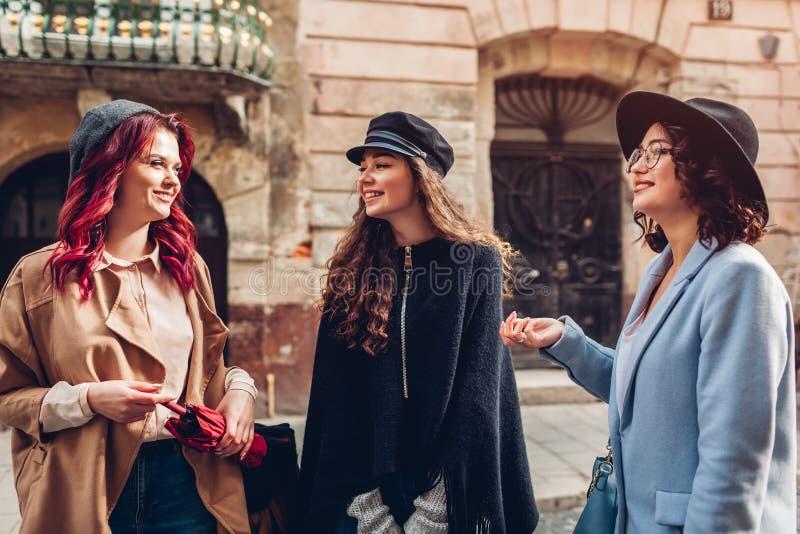 Un colpo all'aperto di tre giovani donne alla moda che parlano sulla via della citt? Amici che ridono e che hanno divertimento fotografia stock libera da diritti