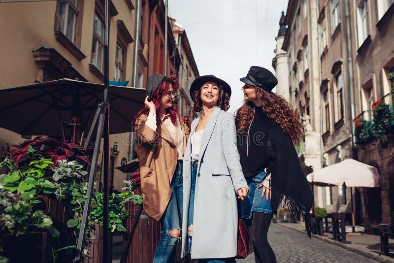 Un colpo all'aperto di tre giovani donne che camminano sulla via della citt? Ragazze che parlano e che abbracciano fotografia stock