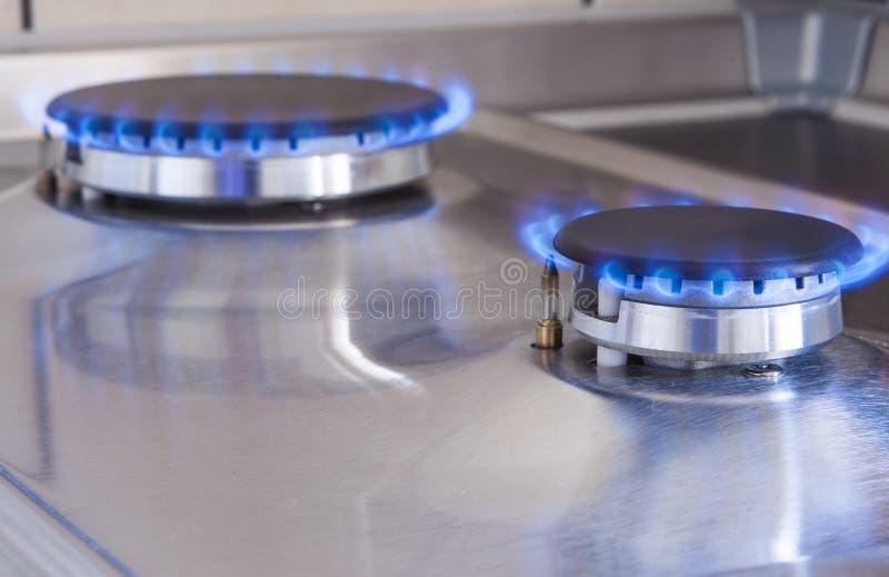 Un colpo del primo piano di due bruciatori a gas nella linea situata sulla stufa di cucina fotografia stock