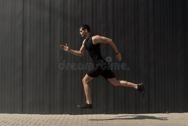 Un colpo di vista laterale di una misura giovane, dell'uomo atletico che salta e che corre fotografia stock libera da diritti