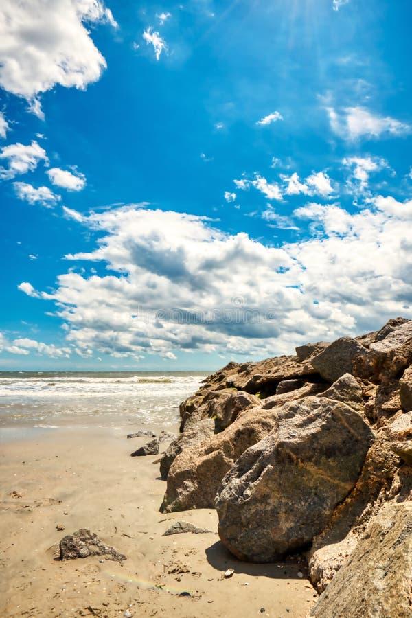 Un colpo grandangolare della spiaggia con un inguine della roccia e un bello cielo immagini stock libere da diritti