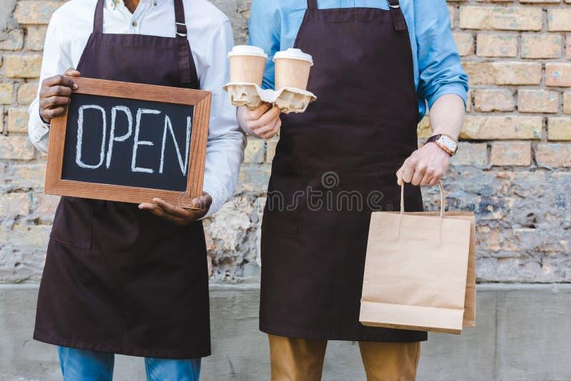 un colpo potato di due proprietari multietnici del segno della tenuta della caffetteria aperto, dei sacchi di carta e delle tazze fotografia stock libera da diritti