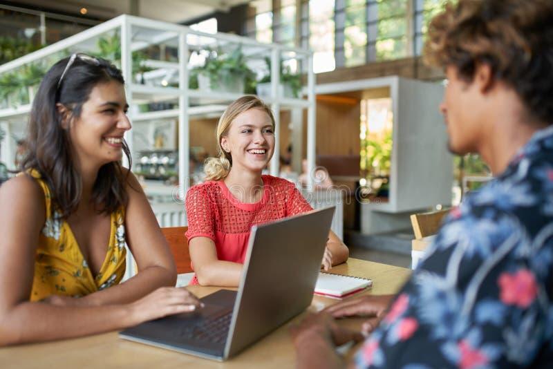 Un colpo schietto di stile di vita di tre giovani diversi amici millenari d'avanguardia che collaborano insieme sul computer port immagini stock