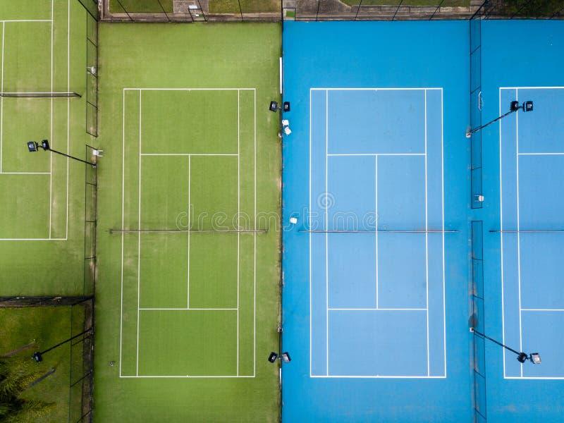 Un colpo sopraelevato aereo di due campi da tennis parallelamente, nessun giocatori fotografia stock