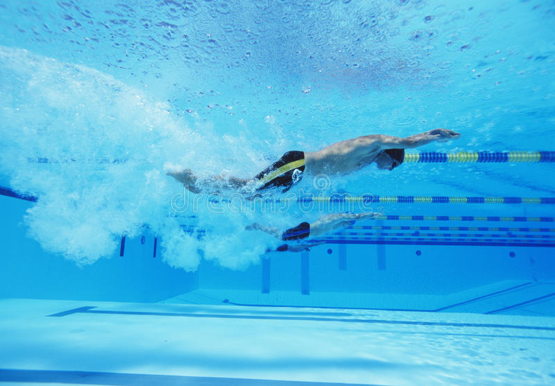 Un colpo subacqueo di tre atleti maschii che corrono nella piscina immagine stock libera da diritti