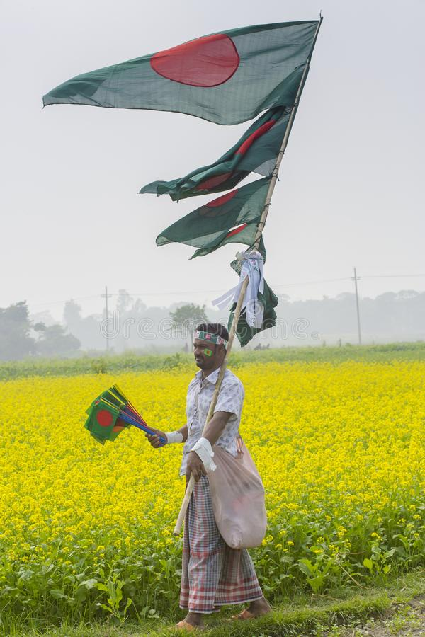 Un colporteur vend les drapeaux nationaux bangladais au champ de moutarde chez Munshigonj, Dhaka, Bangladesh images stock