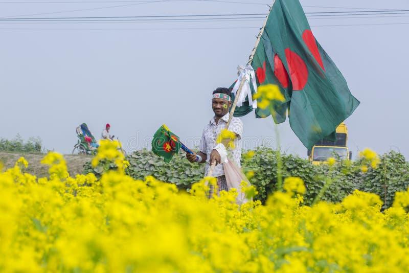 Un colporteur vend les drapeaux nationaux bangladais au champ de moutarde chez Munshigonj, Dhaka, Bangladesh images libres de droits