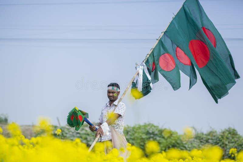Un colporteur vend les drapeaux nationaux bangladais au champ de moutarde chez Munshigonj, Dhaka, Bangladesh image libre de droits