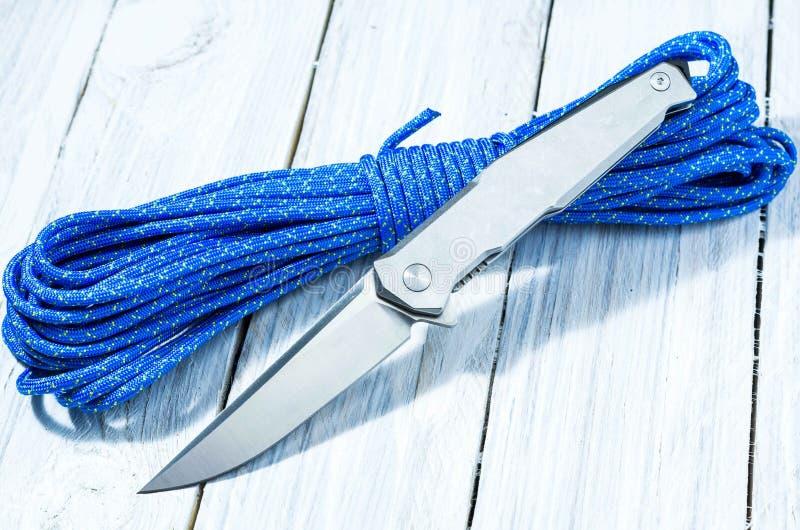Un coltello brillante su un cavo del paracadute facciata frontale immagini stock