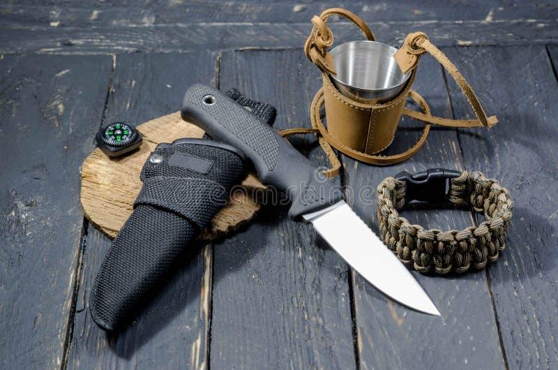 Un coltello militare, un braccialetto di sopravvivenza e un vetro del metallo nella pelle immagini stock