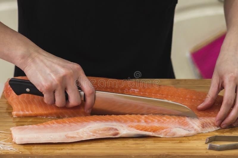 Un coltello per affettare un grande salmone immagine stock