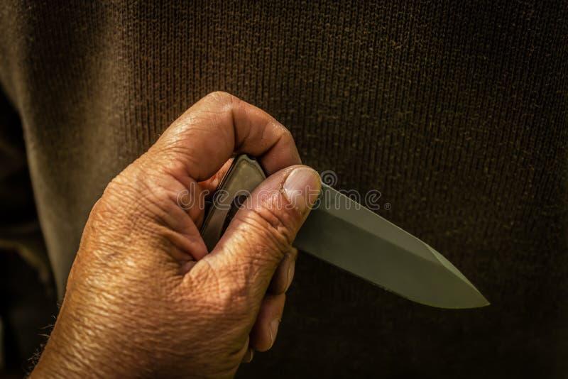 Un coltello a serramanico tagliente dietro alla a equipaggia la parte posteriore immagine stock