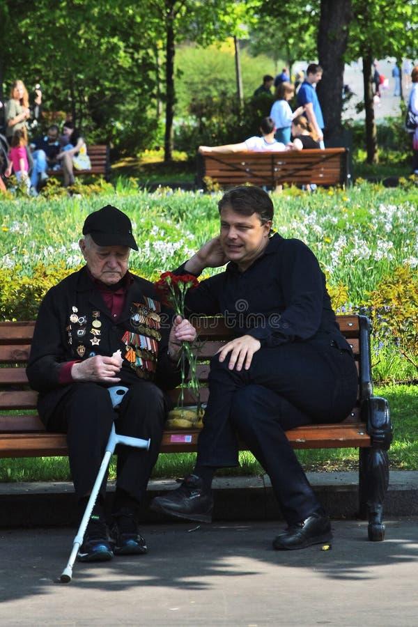 Un combattant s'assied sur un banc par un jeune homme photographie stock libre de droits