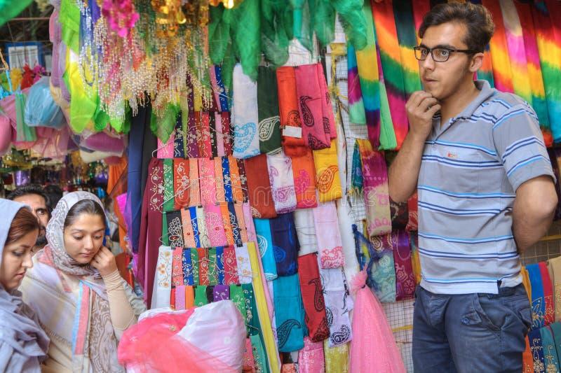 Un commerçant de tissu se tient près de son produit, Chiraz, Iran photo stock
