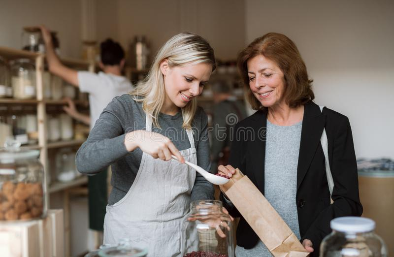 Un commesso femminile che serve un cliente senior in un negozio dello zero-spreco immagini stock libere da diritti