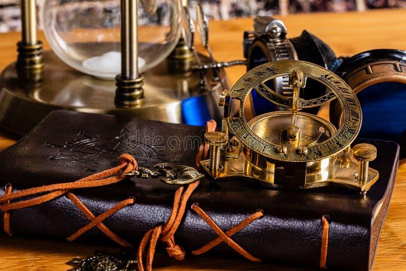 Un compás y un reloj de sol náuticos de cobre amarillo antiguos, con un diario de cuero, gafas y un reloj de arena de cobre amari imagenes de archivo
