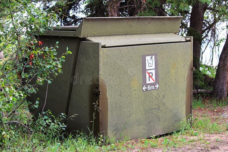 Un compartimiento de basura con una muestra en-delantera del estacionamiento prohibido fotos de archivo libres de regalías