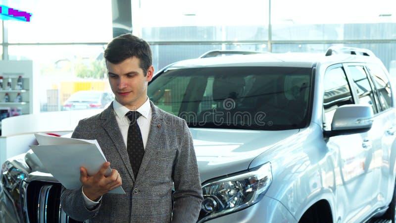 Un comprador feliz presenta un coche de la sala de exposición del automóvil fotos de archivo