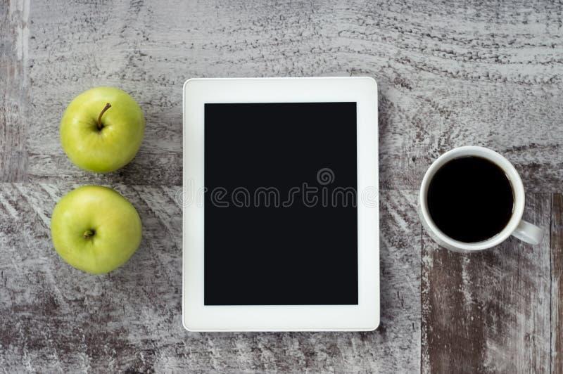 Un comprimé blanc avec une tasse de café et de pommes vertes se trouve sur la table images libres de droits