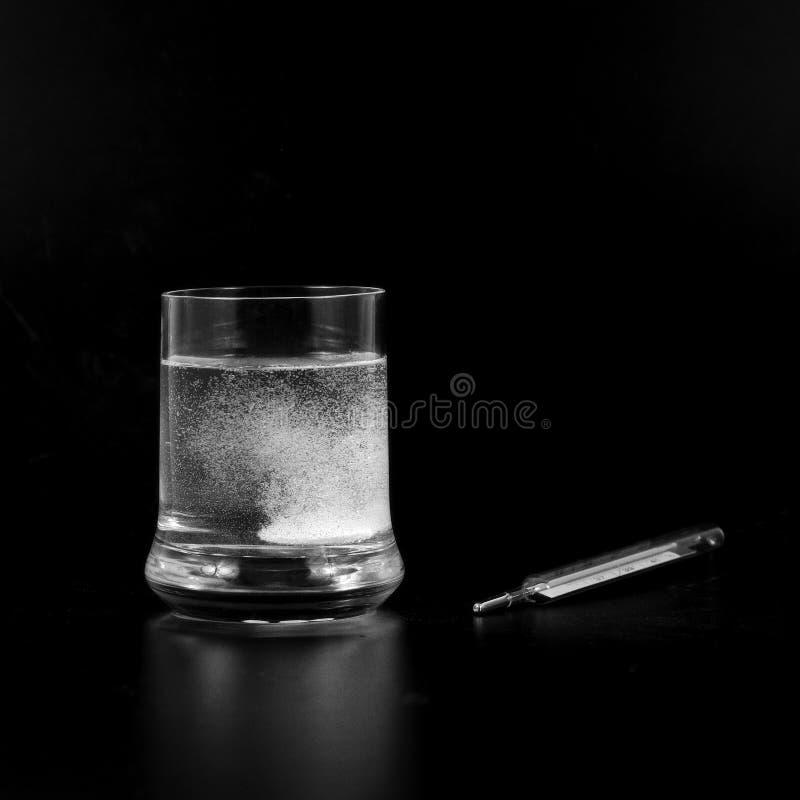 Un comprimé effervescent dans le verre avec un thermomètre près de lui photographie stock