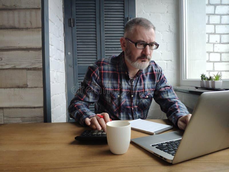 Un comptable masculin travaille sur un ordinateur portable et des comptes sur une calculatrice images stock