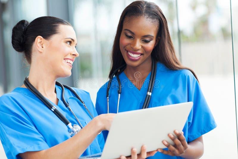 Un computer portatile di due infermieri fotografia stock