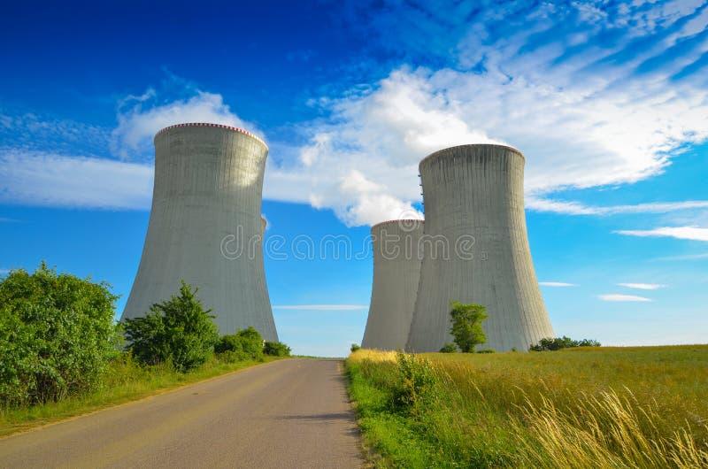 Un concepto de energía verde renovable: una margarita y una hierba sobre el símbolo de la energía atómica quebrada fotos de archivo
