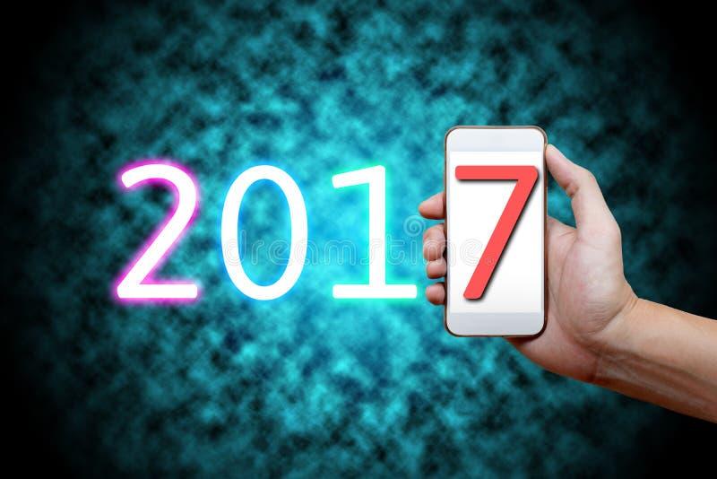 Un concetto di 2017 buoni anni, parte del corpo, fon del cellulare della tenuta della mano immagine stock