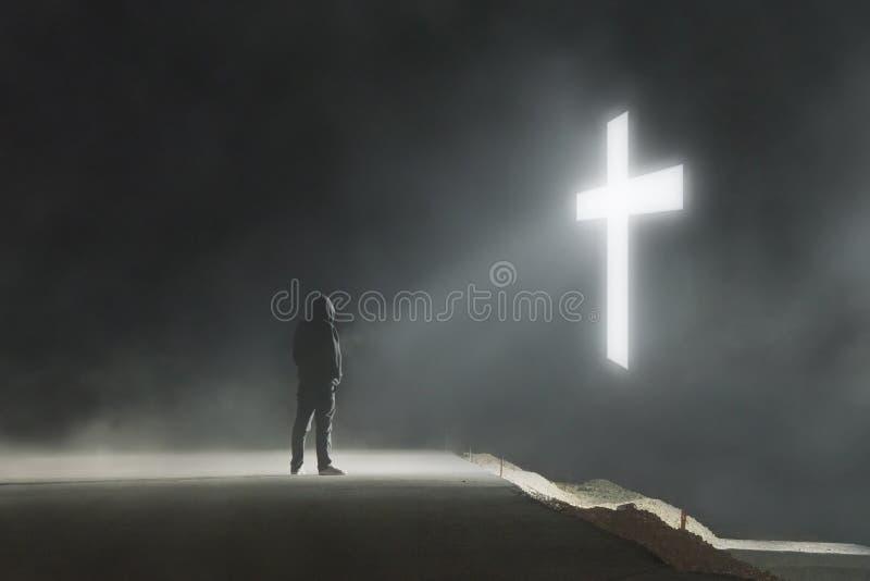 Un concetto digitale di arte di una figura incappucciata che esamina un ardore trasversale su una notte nebbiosa e atmosferica immagini stock