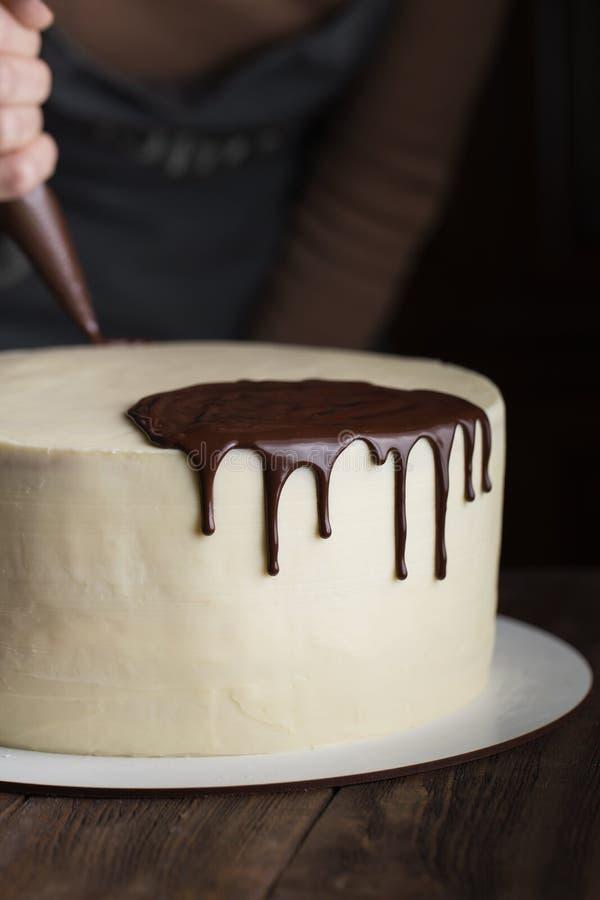 Un confitero exprime el chocolate líquido de un bolso de los pasteles sobre una torta poner crema blanca de la galleta El concept imagen de archivo libre de regalías