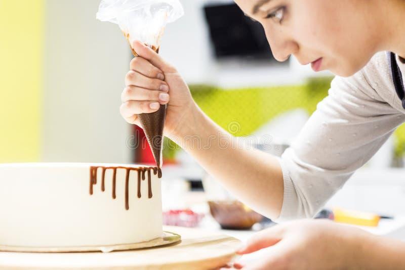 Un confitero exprime el chocolate l?quido de un bolso de los pasteles sobre una torta poner crema blanca de la galleta en un sopo imagenes de archivo