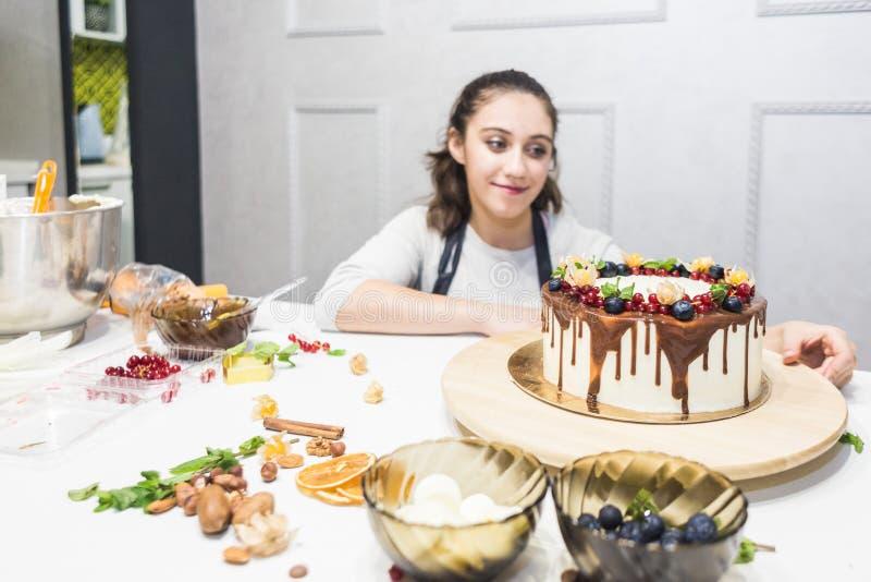 Un confitero se coloca al lado de una torta cocinada de la galleta con la crema blanca, adornada con el chocolate y las bayas Sop imagen de archivo libre de regalías
