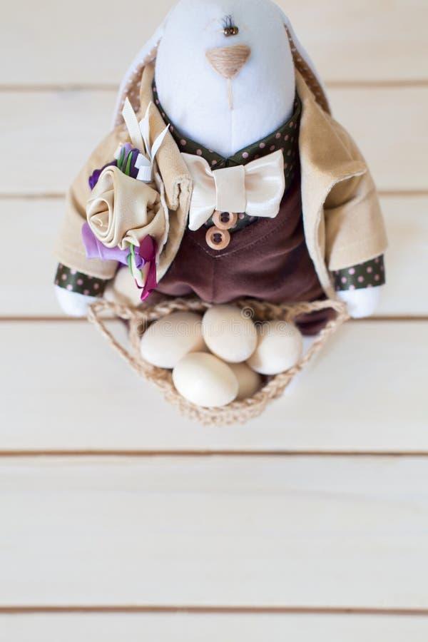 Un coniglio fatto a mano tiene il canestro con le uova di Pasqua Legno bianco fotografia stock