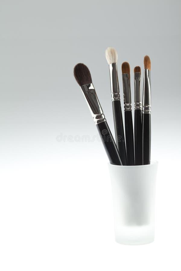 Un conjunto del conjunto de 5 cepillos del maquillaje en un pequeño vidrio imágenes de archivo libres de regalías