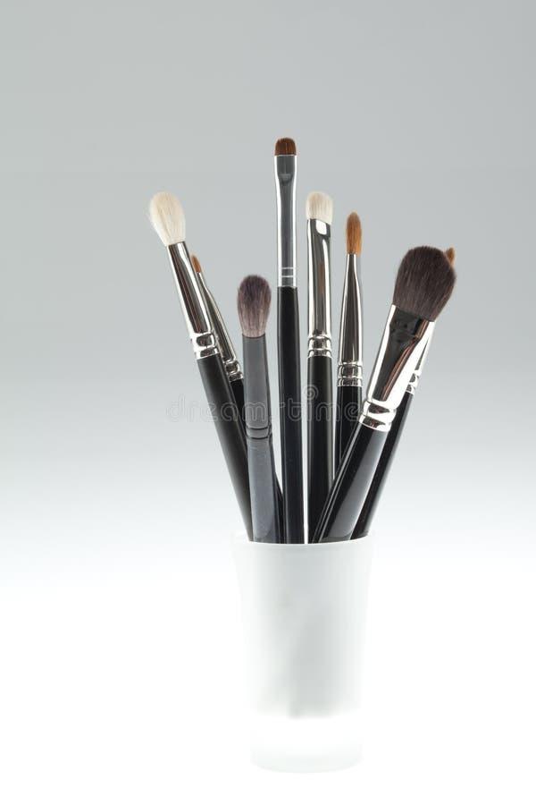 Un conjunto del conjunto de cepillos del maquillaje en un pequeño vidrio fotografía de archivo libre de regalías