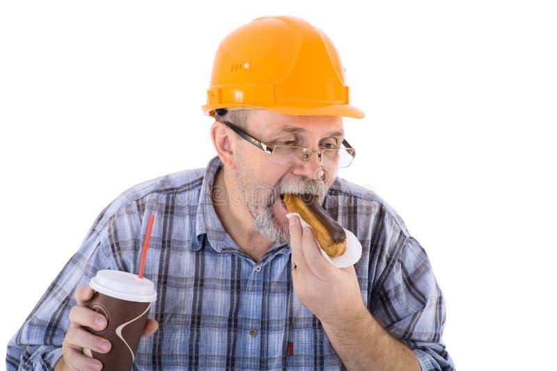 Un constructeur d'homme supérieur prend le déjeuner avec du café et le gâteau photo stock