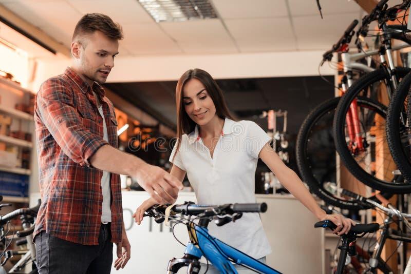 Un consulente in materia della ragazza mostra il compratore in un negozio di biciclette immagine stock
