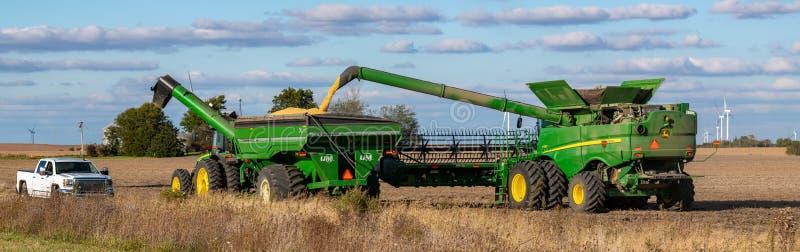 Un contadino prende parcheggiato in un campo vicino al trattore e al tramoggia immagine stock libera da diritti
