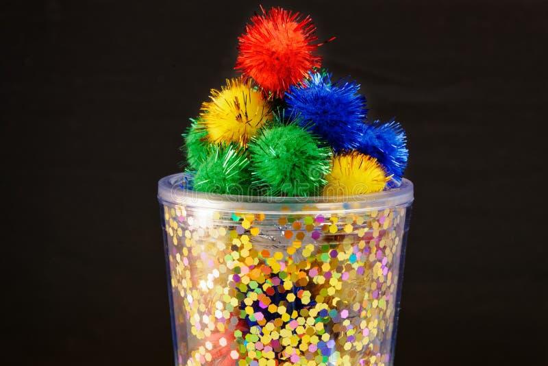 Un contenitore luminoso in pieno dei poms colourful e lanuginosi del pom fotografia stock libera da diritti