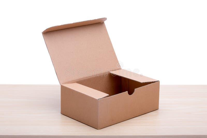 Un contenitore marrone di pacchetto sul bordo di legno blackground bianco fotografia stock libera da diritti