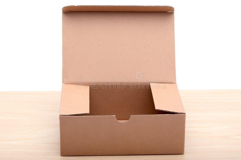 Un contenitore marrone di pacchetto sul bordo di legno su blackground bianco immagini stock libere da diritti