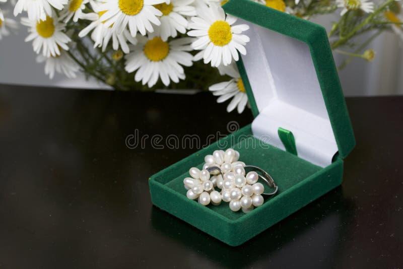 Un contenitore verde aperto di velluto per gioielli In si trova un insieme: un anello ed orecchini con le perle Accanto al vaso è fotografie stock libere da diritti