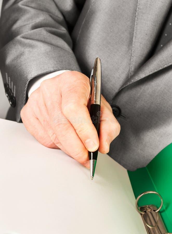 Un contratto di firma dell'uomo d'affari con una penna immagini stock libere da diritti
