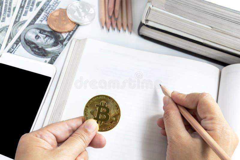 Un control de la mano del ` s de la mujer un bitcoin con el lápiz de madera de los libros de Op. Sys. foto de archivo libre de regalías