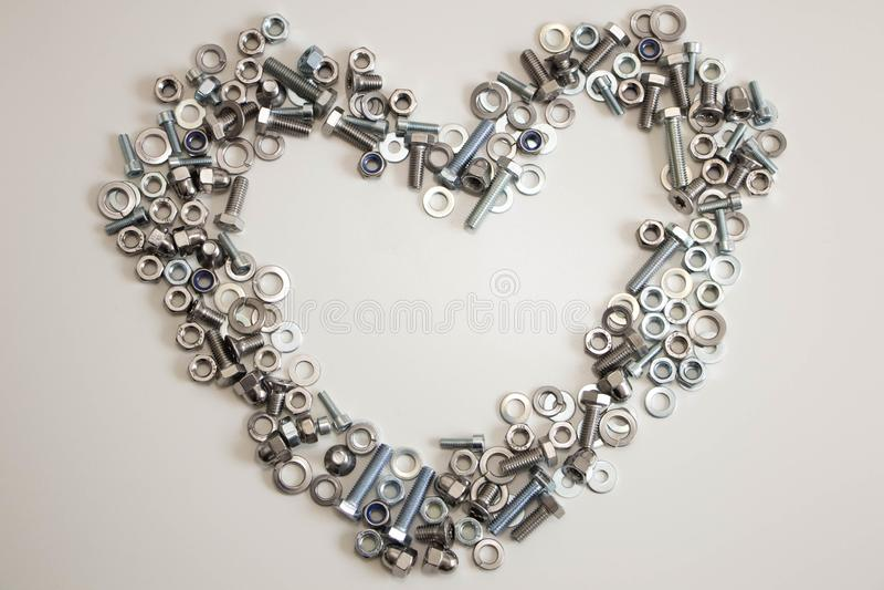 Un corazón alineado con una variedad de nueces, de pernos, de tornillos y de lavadoras con el interior vacío del espacio en un fo imagen de archivo libre de regalías