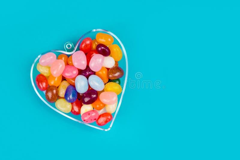 Un corazón con los caramelos en fondo azul imagenes de archivo