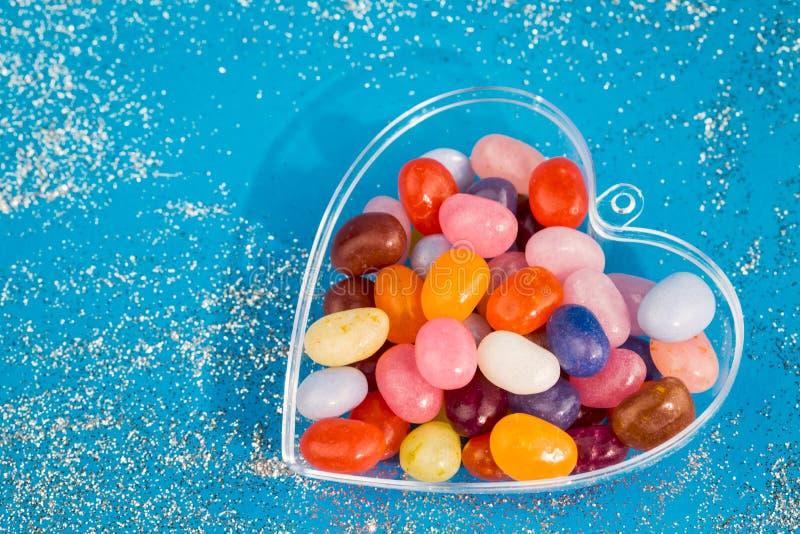 Un corazón con los caramelos en fondo azul imagen de archivo libre de regalías